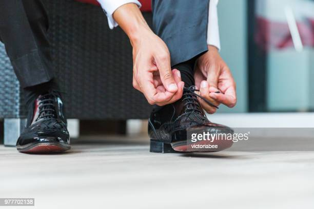 man tying his shoelaces - shoelace stock pictures, royalty-free photos & images