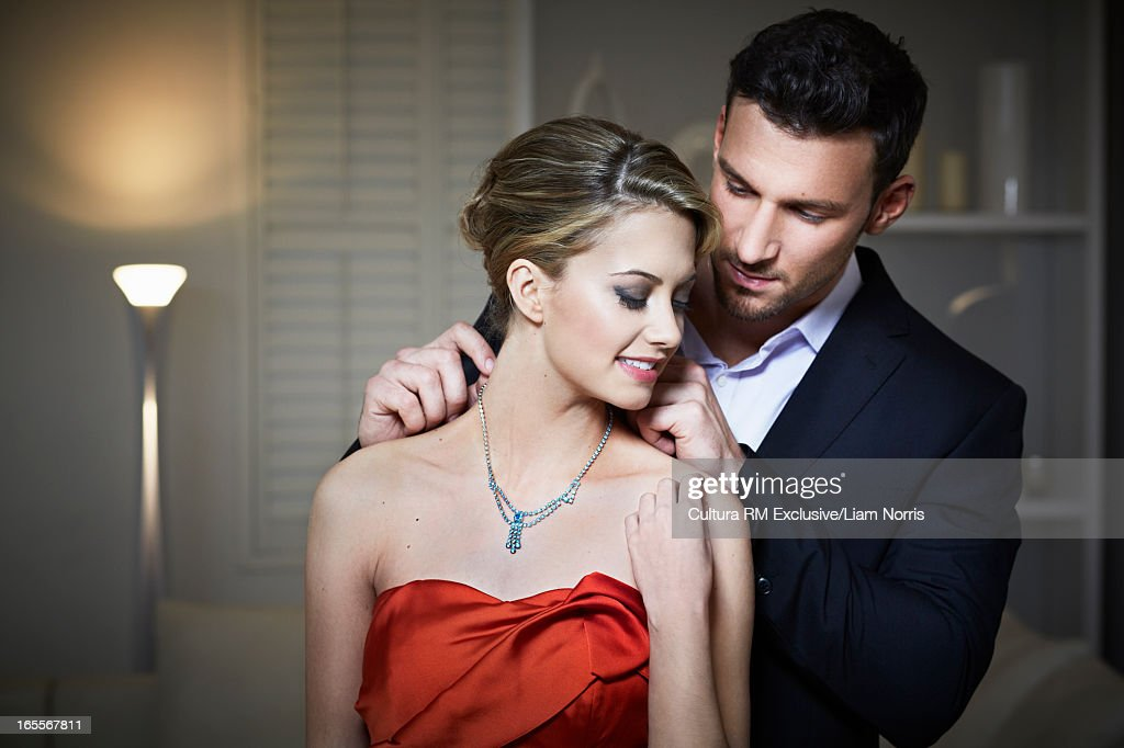 Man tying necklace on girlfriend : Stock Photo