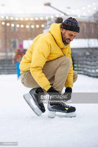 man tying shoelace on snowy land - lace glove stock pictures, royalty-free photos & images