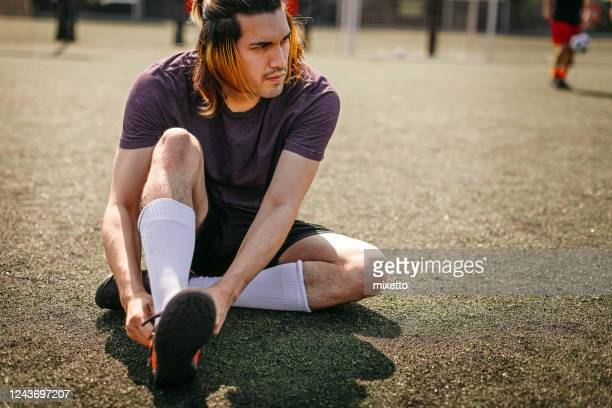 man tying shoelace on sports field - tying shoelace stock pictures, royalty-free photos & images