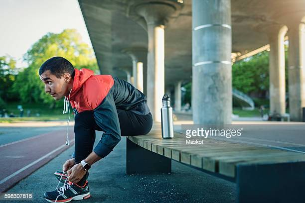 Man tying shoelace while sitting on bench