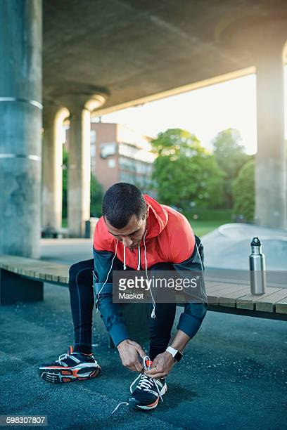 Man tying shoelace while sitting on bench under bridge