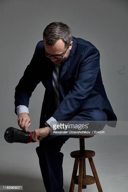 man tying shoelace while sitting on seat against gray background - tying shoelace stock pictures, royalty-free photos & images