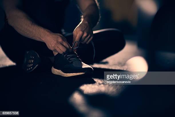 Man tying shoelaces at gym