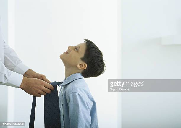 Man tying tie around boy's neck