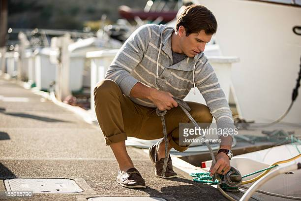 a man tying up a boat at the dock. - moored stock pictures, royalty-free photos & images