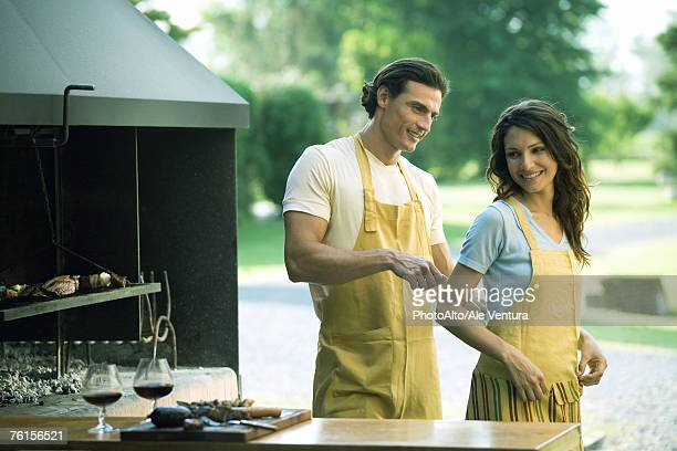 Man tying woman's apron by outside wood oven