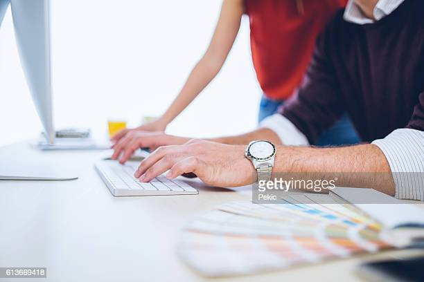 Man typing on computer keyboard, color swatch on desk