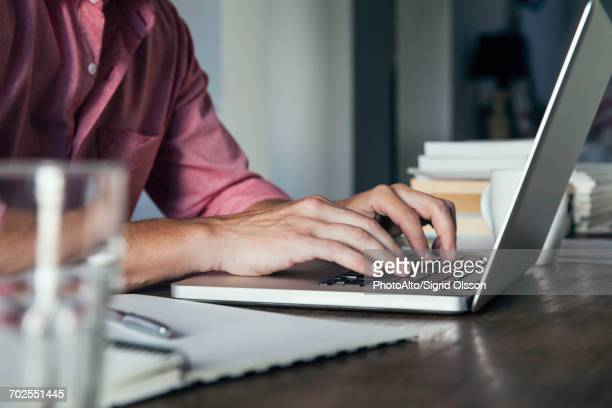 man typing on laptop computer, cropped - authors stockfoto's en -beelden