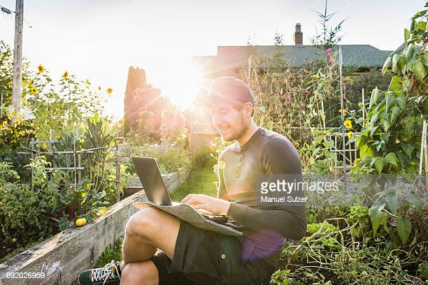 Man typing on laptop in sunlit community garden, Vancouver, Canada