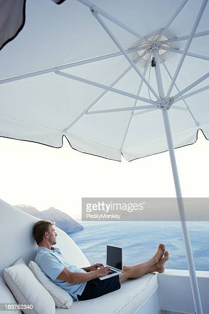 Man Typing on Laptop Overlooking Dramatic Seascape