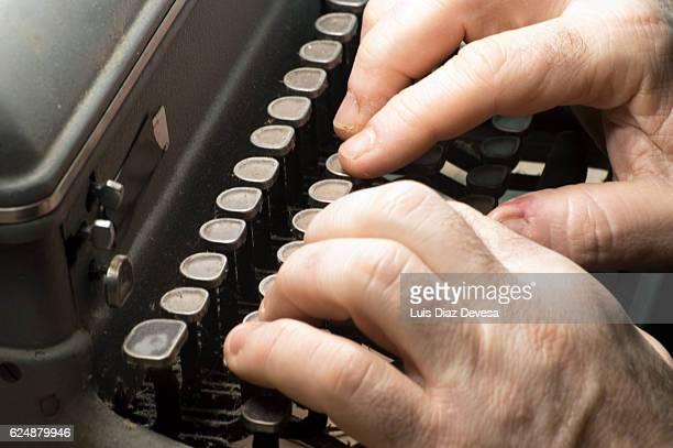 Man typing on manual typewriter,