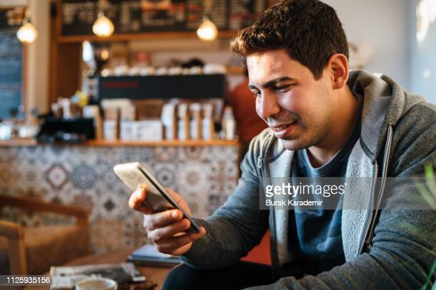 Man typing text message in a coffee shop