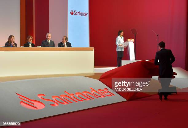 A man uinveils the new logo of Spanish Santander Bank next to Executive Chairman Ana Botin during the bank's general shareholders meeting in...