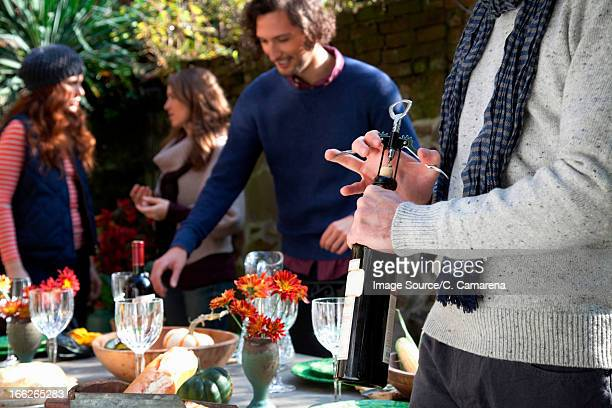 Man uncorking bottle of wine at table