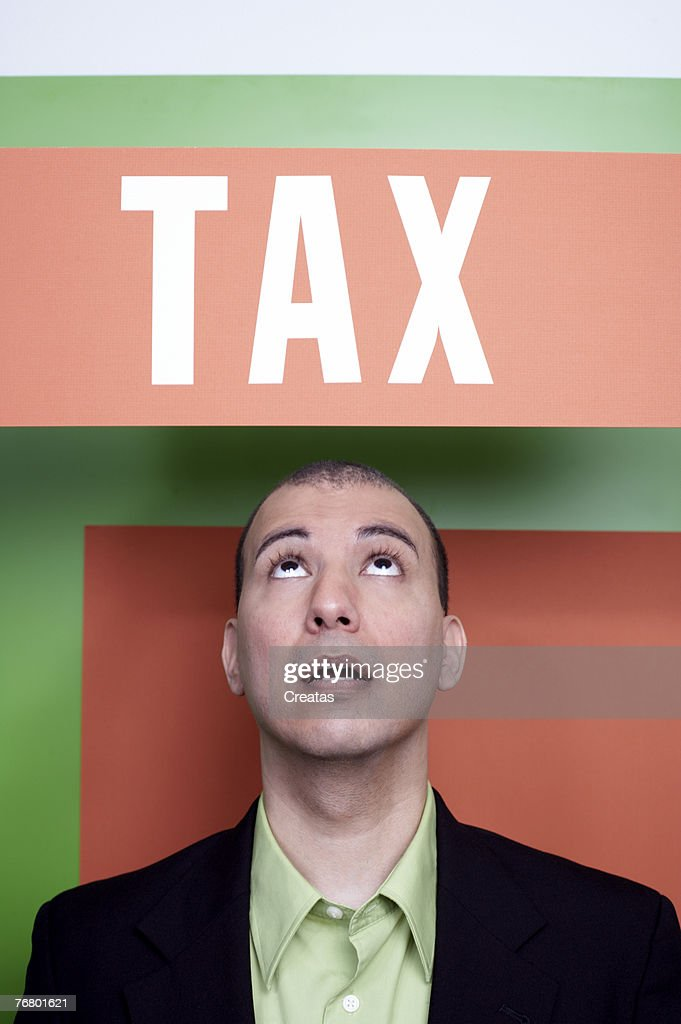 Man under a tax sign : Stock Photo