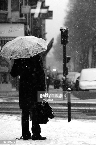 CONTENT] Man under an umbrella in a Paris Avenue It's snowing