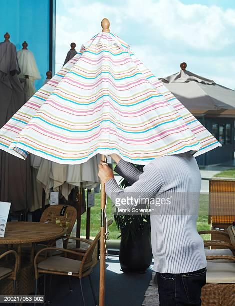 Man under parasol in garden centre