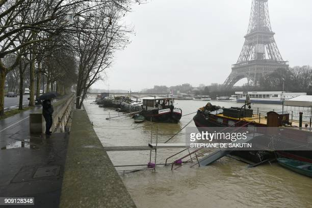 A man under un umbrella looks at houseboats docked at a flooded bank as the river Seine level has risen in front of the Eiffel tower in Paris on...