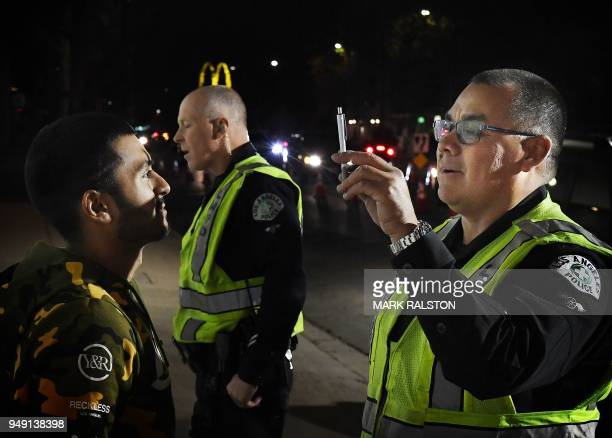A man undergoes a sobriety test before being detained at a LAPD police DUI checkpoint in Reseda Los Angeles California on April 13 2018 Pot may be...