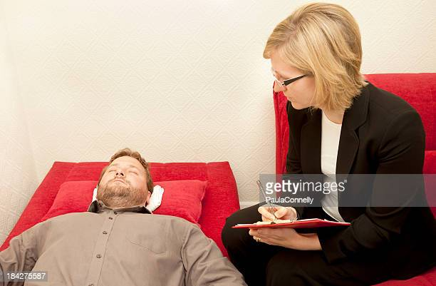Man undergoing hypnotherapy and a woman surveying him