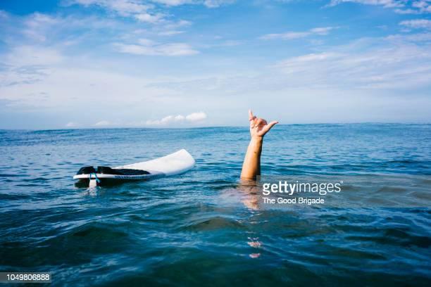 man underwater giving shaka sign near surfboard - geisteshaltung stock-fotos und bilder