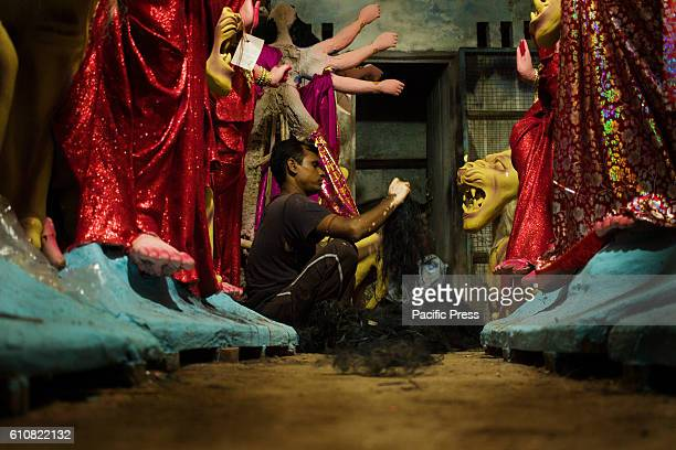 A man unfolding artificial hair for idols With Durga Puja round the corner preparations are in full swingDurga Puja is the most important festival of...