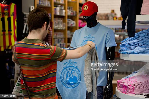 A man unfolds a tshirt featuring Prince Felipe and Princess Letizia as future monarchs of Spain in front of a mannequin at a merchandising store on...