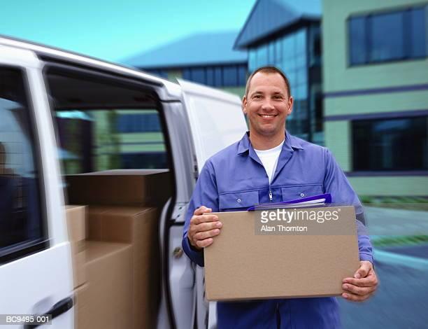 Man unloading boxes from white van, portrait (Enhancement)
