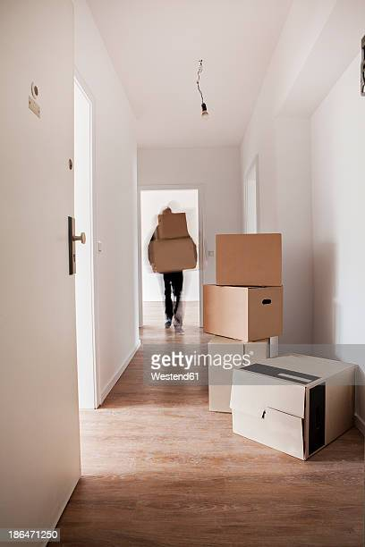 Man unloading cardboard boxes in new house