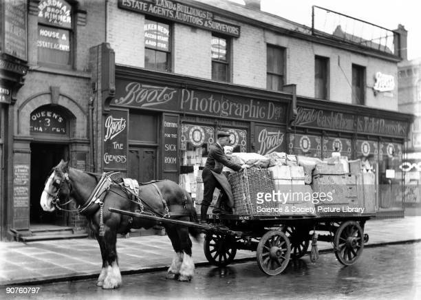 Man unloading goods from a cart in front of a Boots store where photographic developing is available as well as �Everything for the sick room� and...