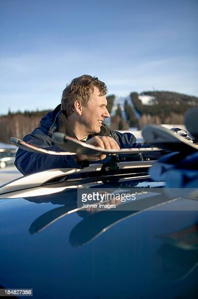 Man unloading skis from roof rack