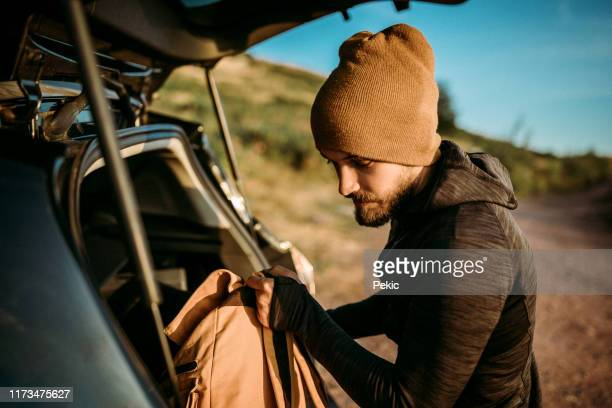 man unloading the car trunk packed with luggage for road trip - car trunk stock pictures, royalty-free photos & images