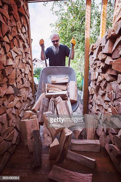 Man unloading wheelbarrow full of firewood
