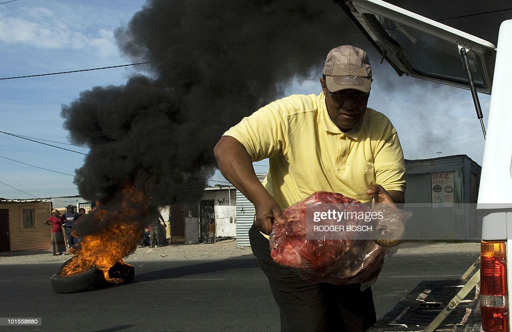 A man unloads meat as tyres, which were set alight during service delivery protests, burn behind him on June 2, 2010, in Monwabisi Park, Khayelitsha, about 30Km from the centre of Cape Town. South African police on June 1, 2010 arrested 26 protestors who burned tyres, threw stones and blocked roads over the removal of open-air toilets which have caused a stink for Cape Town officials. Police reacted to three separate uprisings in Khayelitsha, a poor shack-filled area in the east of the city, firing rubber bullets at two of the crowds.