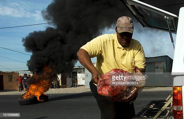 A man unloads meat as tyres which were set alight during service delivery protests burn behind him on June 2 in Monwabisi Park Khayelitsha about 30Km...