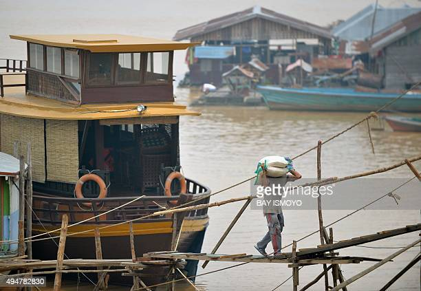 A man unloads sacks of rice from a ship at the riverport in Palangkaraya in Central Kalimantan on October 29 2015 as residents enjoy clearer skies...