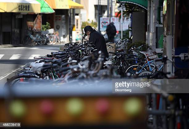 A man unlocks his bicycle in the Airin area of Nishinari ward in Osaka Japan on Friday May 2 2014 Osaka prefectur's economic output dropped 62...
