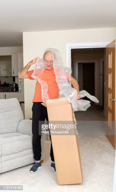 man unpacking a brown cardboard box containing an excessive amount of protective air bags - airbag stock-fotos und bilder