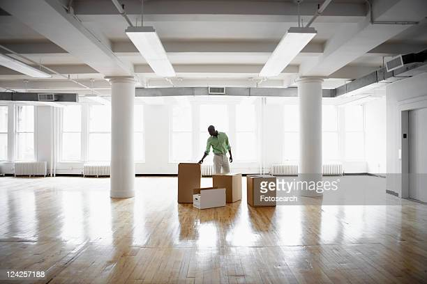 man unpacking boxes in empty office - endopack stock pictures, royalty-free photos & images