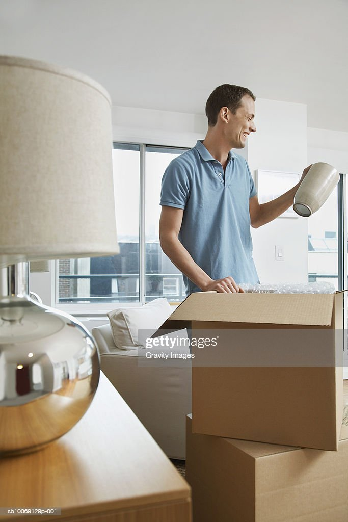 Man unpacking cardboard boxes, smiling : Stockfoto