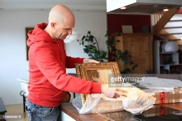 man unpacking online purchase on kitchen counter - painted image stock pictures, royalty-free photos & images