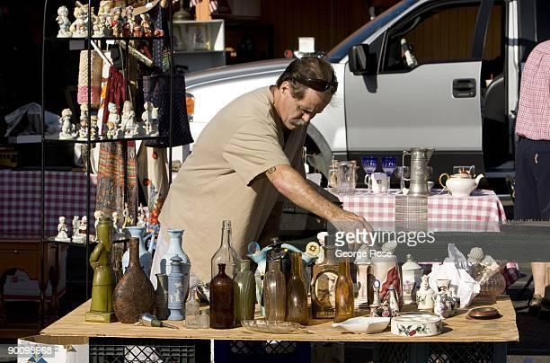 A man unpacks old glass bottles at an open air antique flea market near the downtown square as seen in this 2009 Healdsburg California morning summer...