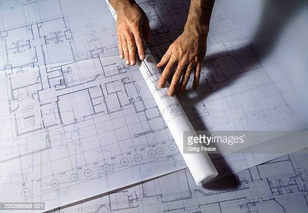 Man unrolling architectural plans, close-up