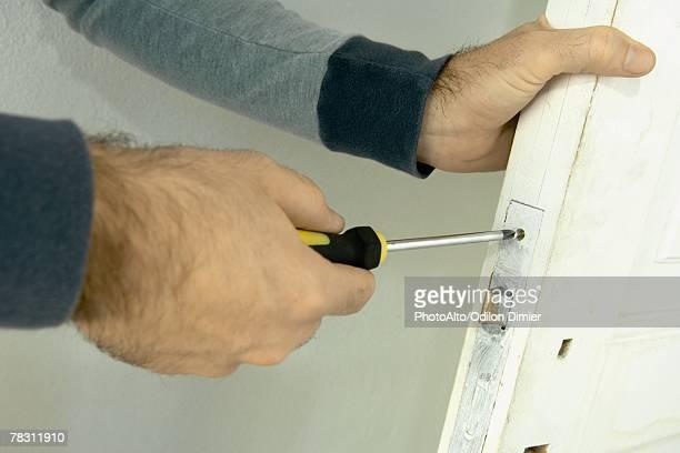 Man unscrewing look on door, close-up of hands