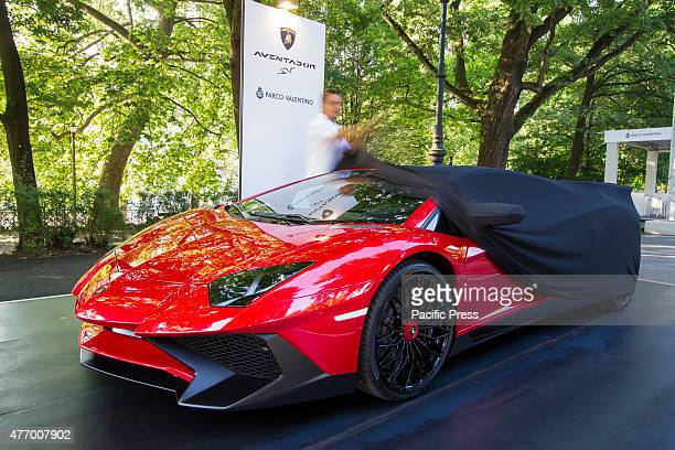 A man unveils a Lamborghini Aventador Parco Valentino car show hosted 93 cars by many automobile manufacturers and car designers inside Valentino Park