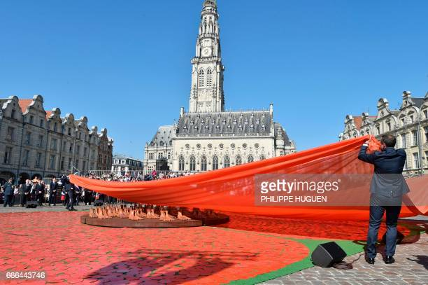 A man unveils the Victory MedalPoppy of Peace installation by New Zealander artists Helen Pollock and Tony McNeight on the Heroes Square in Arras on...