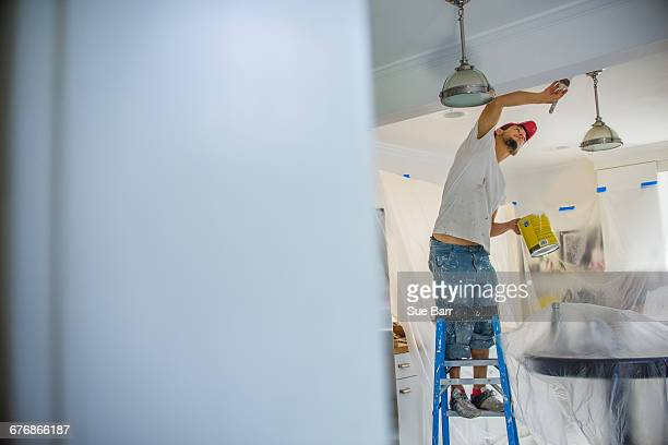 Man up stepladder painting ceiling