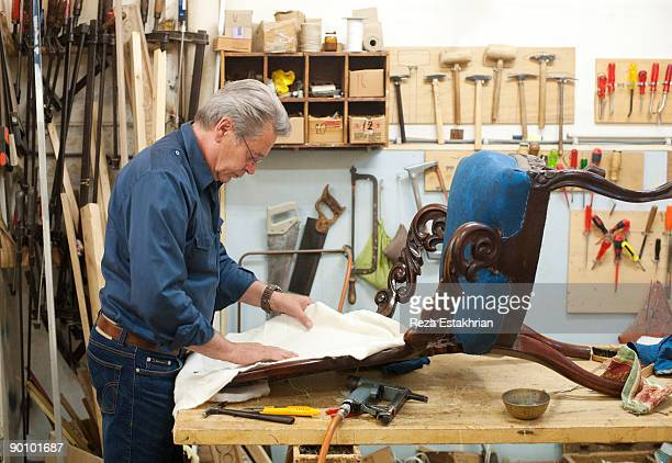 Man upholstering antique chair