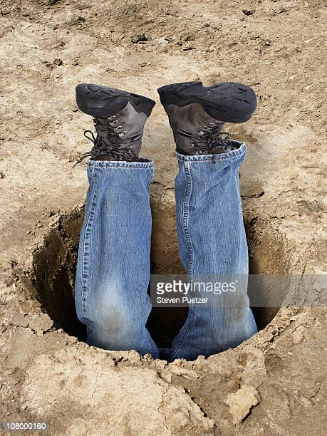 Man upside down in dirt hole with legs in the air